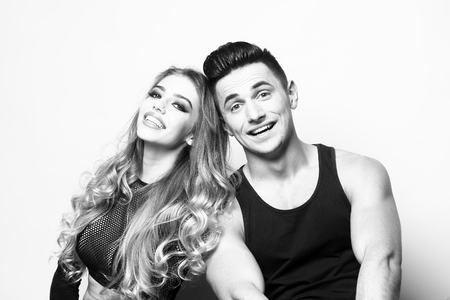 sexual relations: Young couple of muscular boy and sexy girl smiling and sitting in studio, black and white