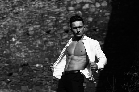 barechested: Man bare-chested young handsome sensual model in shirt gaped open looks at camera poses outside black and white on masonry background