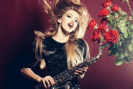 saxof�n: Mujer joven con la cara bonita feliz celebraci�n de saxof�n con el ramo de flores color de rosa Foto de archivo