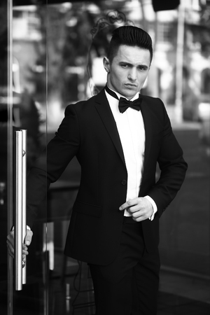 white suit: Confident businessman, black and white. Young man wears suit and bow tie with confidence.