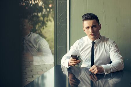 wears: Man young handsome elegant model wears white shirt black skinny necktie with smart phone sits at table reflects in glass window and looks in camera indoor on grey background