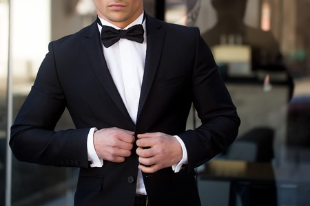 Man young handsome elegant unbuttons suit coat with bow tie at glass entrance door on urban background Archivio Fotografico
