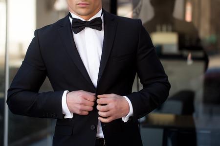 Man jonge knappe elegante unbuttons pak jas met vlinderdas op glazen toegangsdeur op stedelijke achtergrond
