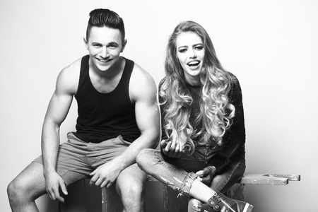 sexual relations: Beauty and fashion, friends. Young couple sitting in studio, black and white