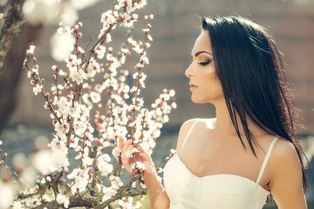 Frühling-Mode-Mädchen im Freien Porträt Bäume in Blüte. Schönheit Romantische Frau in den Blumen. Sensual Lady. Schöne Frau, die Natur genießen. Romantische Schönheit in der Phantasie Obstgarten