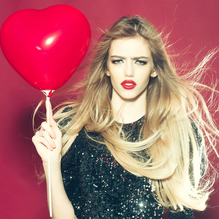 sexi: Young woman with emotional face and heart balloon Stock Photo