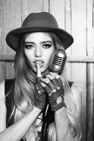 sexi: Young fashionable woman with pretty face singing in retro microphone, black and white