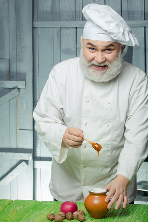 man nuts: Bearded man cook in chef hat with apple nuts and honey on wooden background Stock Photo