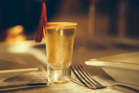 alcoholic drink: Alcoholic drink in small glass decorated with a red chili pepper.
