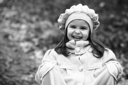adn: Pequeña muchacha en capa y el sombrero que se coloca en el bosque de otoño. infancia feliz, caminando al aire libre, negro del ADN blanco