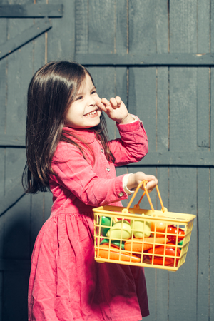 kindergarden: Kindergarden, childhood. Little girl with vegetables and fruit made of plastic in basket. Stock Photo
