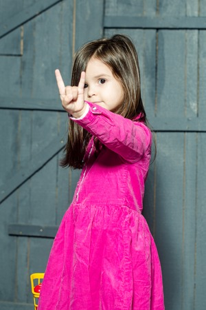 nonverbal communication: Little girl in pink dress shows horns (love hard rock) gesture sign and gesture concept Stock Photo
