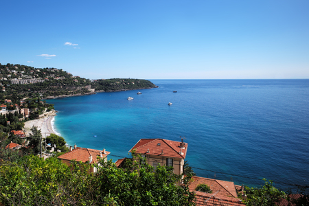 waters: Monte Carlo, Monaco - September 20, 2015: houses villas with terracotta tiled roofs and yachts vessels offshore seacoast coastal waters of beautiful blue sea on seascape background