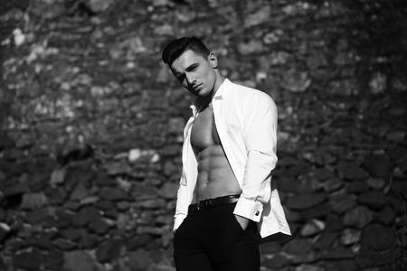poses de modelos: El hombre joven y guapo modelo sensual con el torso desnudo en camisa se abría posturas abiertas con las manos en el bolsillo de los pantalones se ve en cámara fuera en blanco y negro sobre fondo de mampostería Foto de archivo