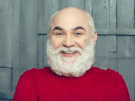 white beard: Senior man. Portrait of smiling happy man with white beard over a wooden background Stock Photo