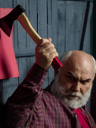white beard: Senior man. Old man with white beard holding axe on red paper in wooden wall Stock Photo