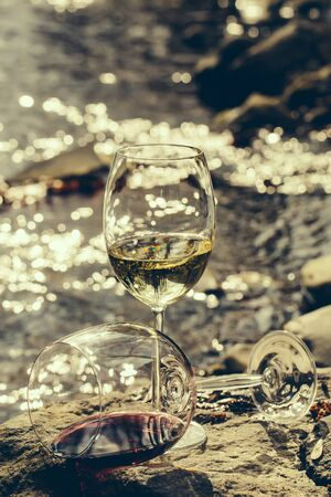 bocal: Wine glass with white wine standing on stone at seashore in sunset. Vintage look Stock Photo