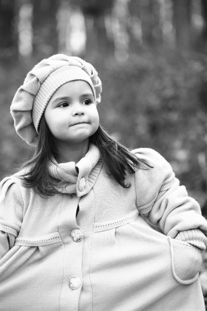 adn: Peque�a muchacha en capa y el sombrero que se coloca en el bosque de oto�o. infancia feliz, caminando al aire libre, negro del ADN blanco