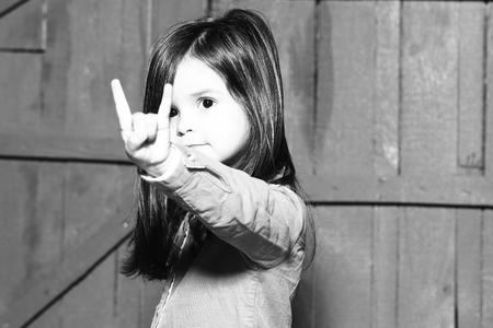 comunicacion no verbal: La niña muestra cuernos (amor de hard rock) signo gesto y el gesto concepto, en blanco y negro Foto de archivo
