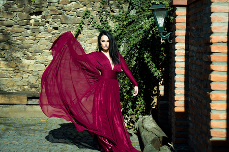 fluttering: Young beautiful woman with brunette hair in fluttering red dress outdoor near brick stony wall Stock Photo