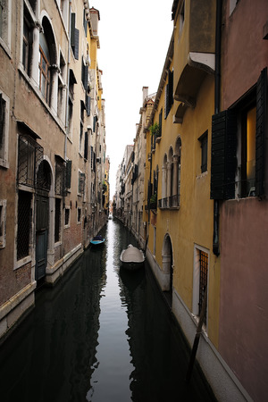 townscape: Venice, Italy - September 22, 2015: venetian canal narrow street between old aged residential buildings and boats at moorings in sea lagoon on townscape background, vertical picture