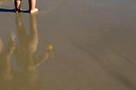 Reflection in sea beach water on wet sand of small child boy standing on coast sunny day outdoor with no people on natural background, copy space, horizontal picture