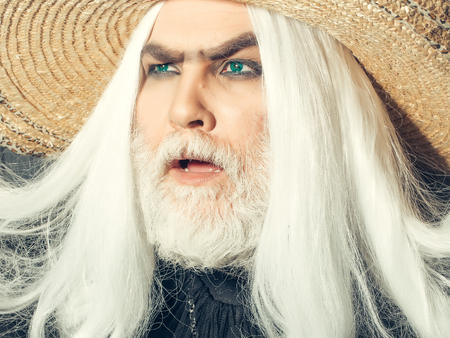 periwig: Bearded senior man in long white wig and straw round hat on wooden background