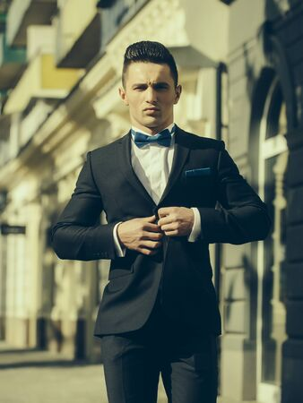 coat and tie: Man young handsome elegant unbuttons suit coat with bow tie outdoor on urban background
