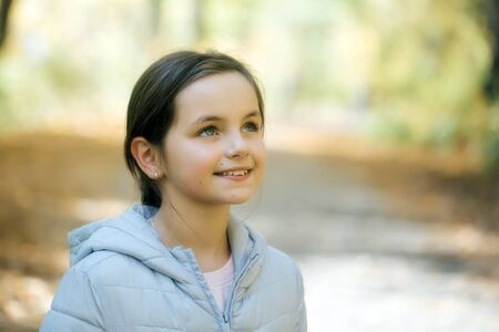 youthful: Cute youthful girl with beautiful eyes and smiling face posing in park on natural background