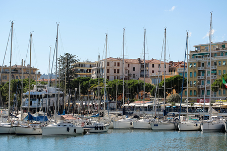 inshore: Monte Carlo, Monaco - September 21, 2015: luxury sailing boats yachts at moorage in sea port inshore on summer day on cityscape background