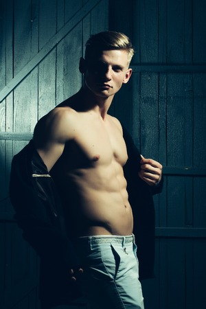 strip shirt: Young man with sexy body showing his muscular torso and abs in open jacket Stock Photo