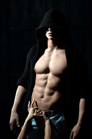 muscular body: Sexy male torso with female hands on muscular body of young man Stock Photo