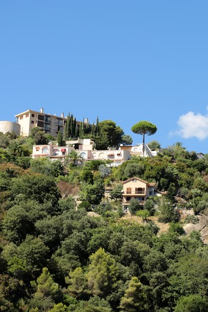 monte carlo: Monte Carlo, Monaco - September 21, 2015: residential buildings among green trees on mountain top on blue sky background
