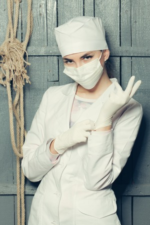 Woman doctor wearing medical gloves in white uniform and mask with rope on wooden wall Reklamní fotografie