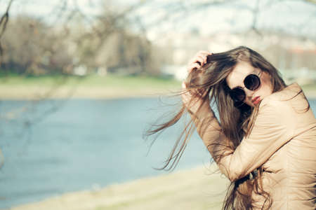 water scape: Stylish girl wearing sunglasses and scarf outdoor in sunny spring or autumn day near water, copy scape