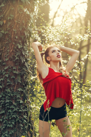 feminity: Pretty young woman with red lips in sport cloths standing in forest near green vine on tree