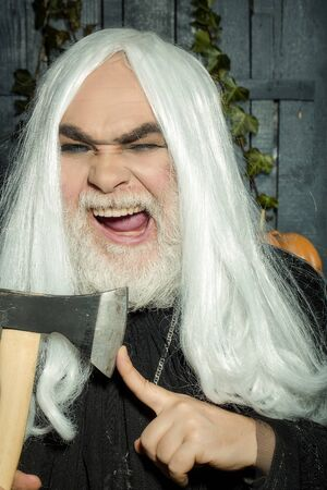periwig: Bearded senior man in long white wig with axe on wooden background