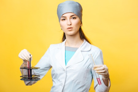 biochemist: Scientist female doctor in medical uniform holding flasks of chemical laboratory in studio on yellow background Stock Photo