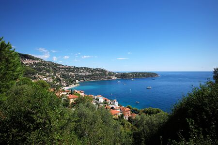 blue vessels: Monte Carlo, Monaco - September 20, 2015: houses villas with terracotta tiled roofs and yachts vessels offshore seacoast of beautiful blue sea on mountain scene