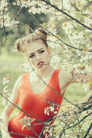 desire: Beautiful sensual young woman enjoying beauty in a flowering spring garden