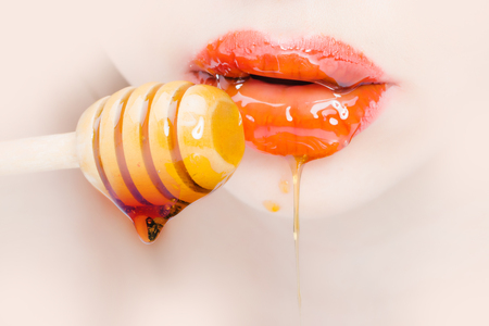 Sensual female red lips eating honey from wooden spoon closeup