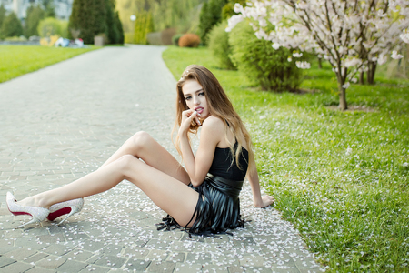 Young girl with beautiful face in glamour leather skirt and diamond shoes sitting on road in blooming park