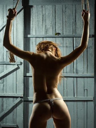 tied woman: Beautiful skimpy  body of young and  woman with tight tied hands in rope standing with buttocks