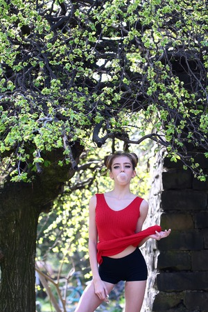 goma de mascar: young pretty woman with chewing gum in the garden with fresh spring leaves on trees on blurred natural background