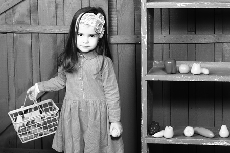 kindergarden: Game, harvest, kindergarden, healthy food. Little girl with plastic vegetables and fruits, black and white