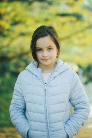 school aged: Beautiful school aged girl brunette with serious face in blue jacket posing in autumn forest on yellow leaves background