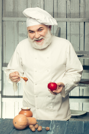 man nuts: Bearded man cook in chef hat with apple nuts pumpkin and honey on wooden background Stock Photo
