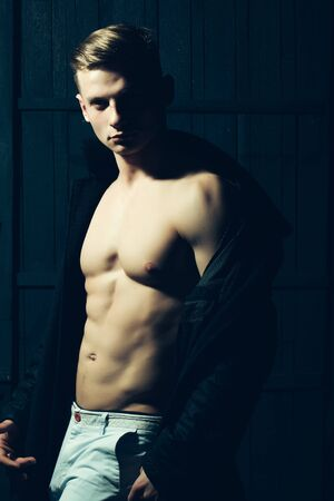 striptease: Young man with  body showing his muscular torso and abs in open jacket