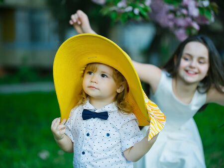 yelloow: Small children of girl in white dress and boy in round yelloow hat and shirt with smiling face in spring on green grass Stock Photo