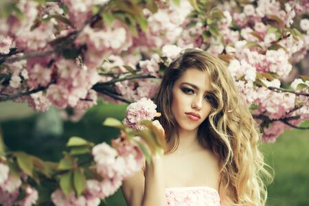 bare shoulders: Beautiful young woman with long curly hair and bare shoulders in spring pink flowers bloom